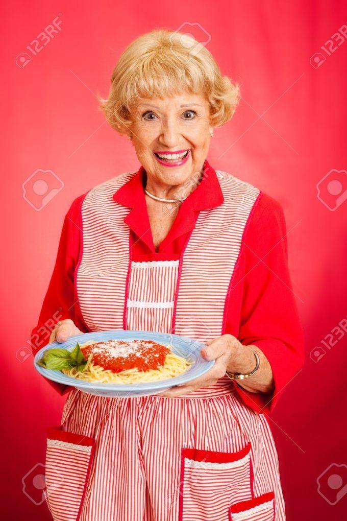 16144062-Sweet-retro-grandmother-holding-a-plate-of-fresh-hot-Italian-Spaghetti-with-marinara-sauce-Red-backg-Stock-Photo