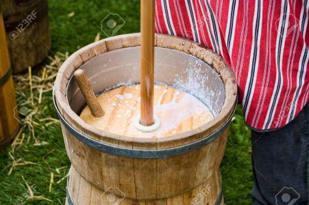 man making butter in a plunger-type butter churn