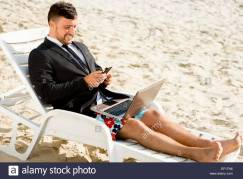 businessman-dressed-in-suit-and-shorts-working-with-laptop-on-the-EF1TN6