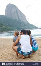 family-on-beach-with-sugarloaf-mountain-rio-de-janeiro-brazil-DPAH0H