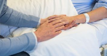 Man-holding-hands-of-his-mother-in-hospital-bed