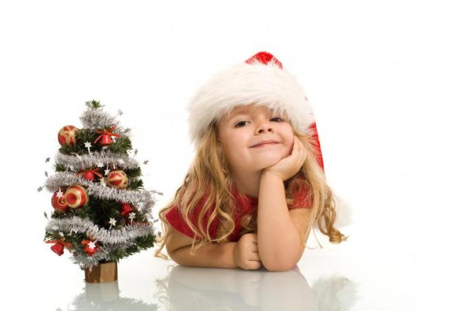 little-girl-with-small-christmas-tree-on-the-table-dreaming-about-the-holidays-isolated-copy-space