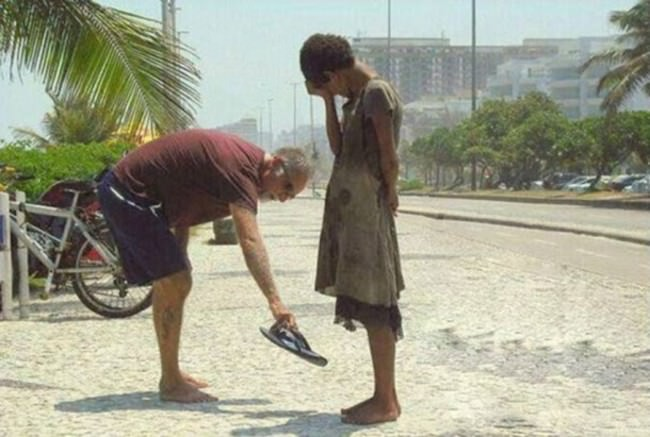 A-man-giving-a-homeless-woman-his-shoes
