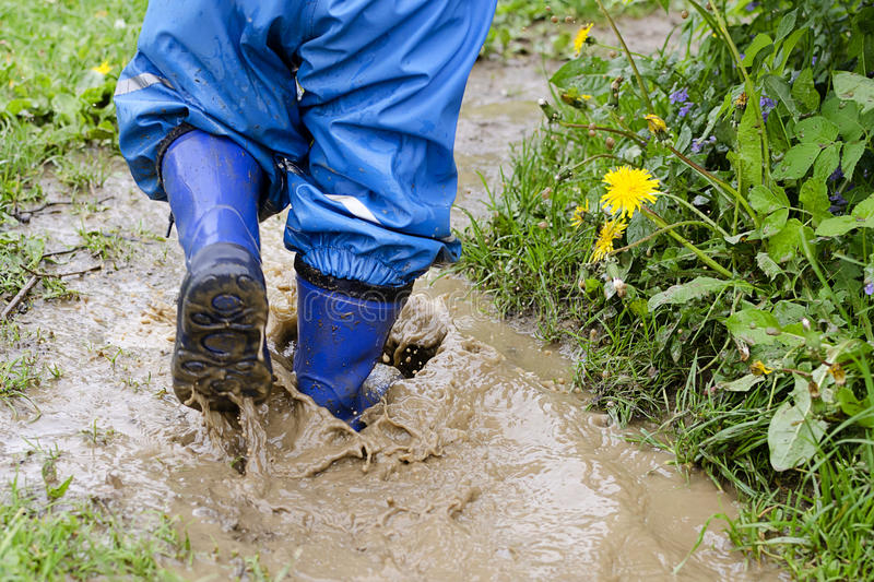 child-puddle-boots-walking-jumping-muddy-rain-31002628