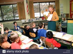 female-teacher-stands-in-front-of-a-3rd-grade-class-in-a-question-AHT52E