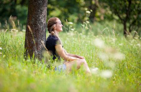 87513966-relaxed-young-girl-sitting-under-tree-on-meadow-at-summer-day