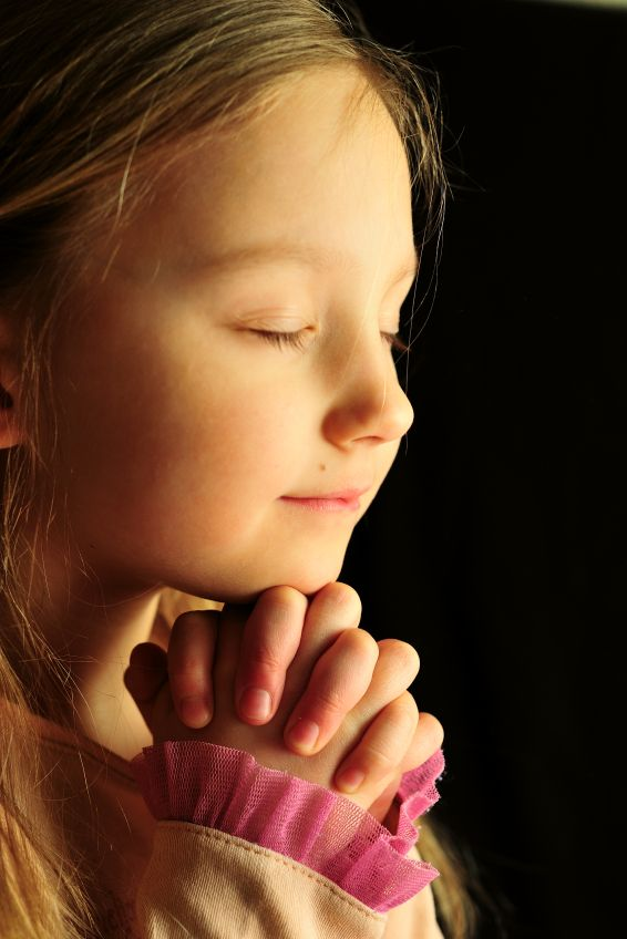 Little girl praying, eyes closed