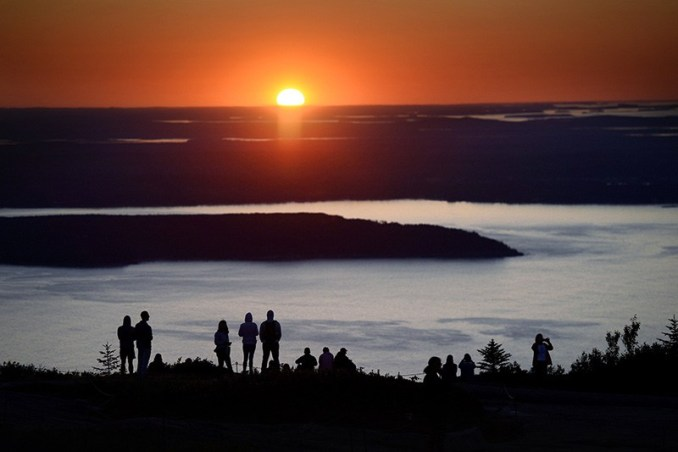 Hundreds of visitors flock to the top of Cadillac Mountain in Acadia National Park to watch the sunrise