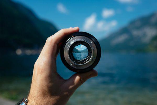 hand-holding-camera-lens-over-landscape-focus-concept