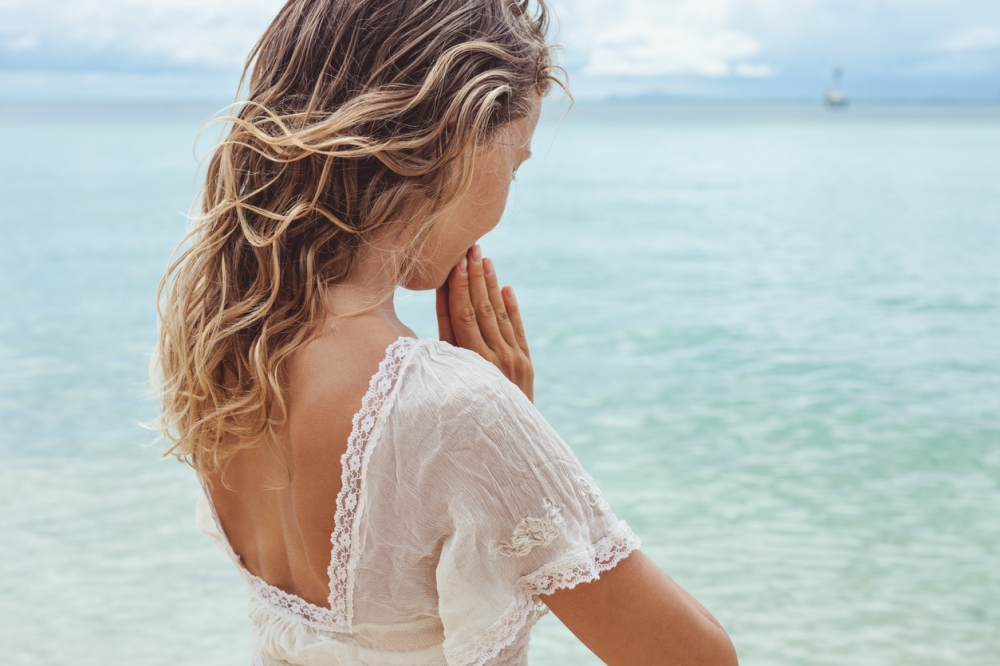 Beautiful young woman praying on the beach